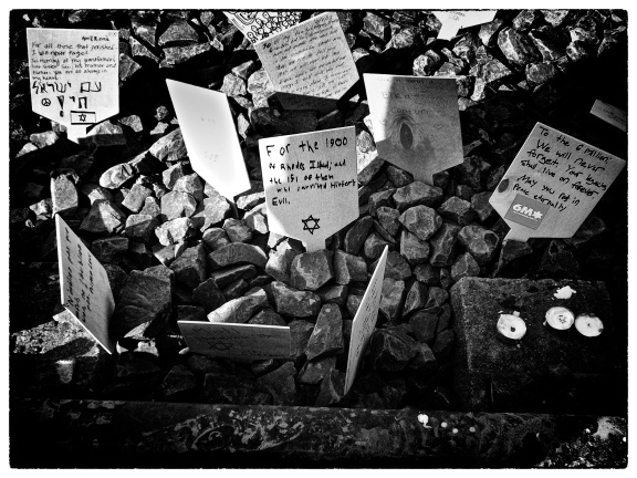 Handwritten signs left on the railway track to Auschwitz. (Middle sign and Photograph by Noah Botman, April 2013)
